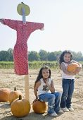 stock photo of scarecrow  - Hispanic sisters with pumpkins and scarecrow - JPG