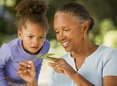 foto of caterpillar  - African grandmother and granddaughter looking at caterpillar - JPG