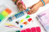 pic of loom  - Young woman make rubber band bracelet with a loom - JPG