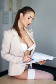 stock photo of secretary  - Sexy brunette secretary in underwear on desk reading catalog - JPG