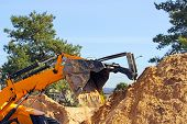 picture of wheel loader  - Wheel loader Excavator unloading sand with water during earth moving works at construction site - JPG