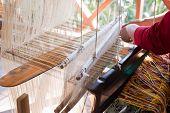 pic of handloom  - Woman weaving silk in traditional way at manual loom. Laos ** Note: Shallow depth of field - JPG