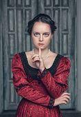 stock photo of dress-making  - Portrait of young beautiful medieval woman in red dress making silence gesture - JPG
