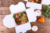 stock photo of chinese parsley  - Chinese noodles in takeaway boxes with mushrooms and parsley on wooden background - JPG