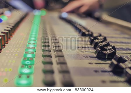 Blurred Hand on a mixer operating the leader on a concert
