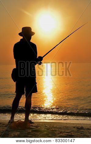 Fisherman silhouette on the beach at sunset