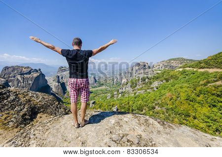 Man with wide open hands on top of a mountain