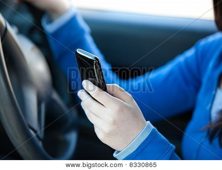 Close-up Of A Teenager Sending A Text While Driving