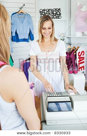 Positive Saleswoman Standing Behind The Counter Using The Cash Register