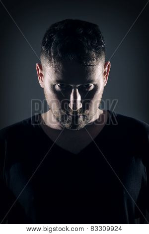 Man posing with angry face and dark background