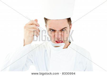 Caucasian Cook Tasting A Soup Doing A Grimace