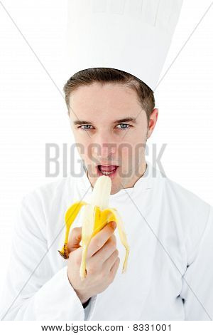 Confident Male Cook Eating A Banana