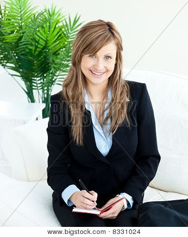 Positive Young Businesswoman Taking Notes Smiling At The Camera