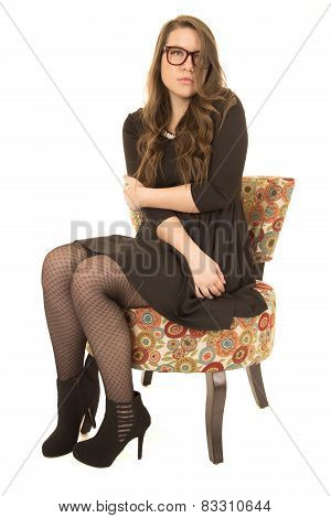 Coy Female Model Wearing Black Dress And Glasses Sitting Down