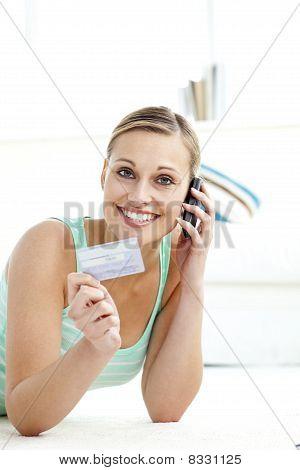 Jolly joven hablando por teléfono con una tarjeta de