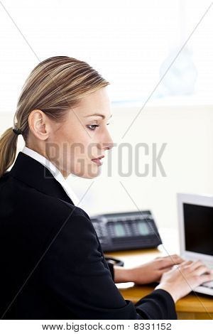 Serious Young Businesswoman Using Her Laptop