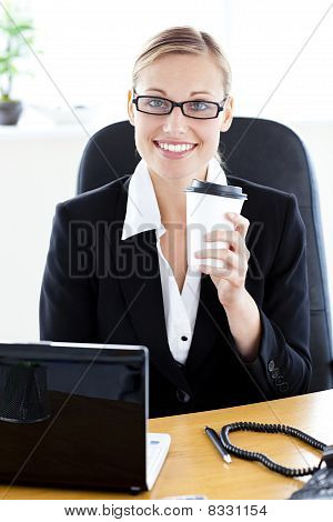 Delighted Caucasian Businesswoman Holding A Coffee Smiling At The Camera