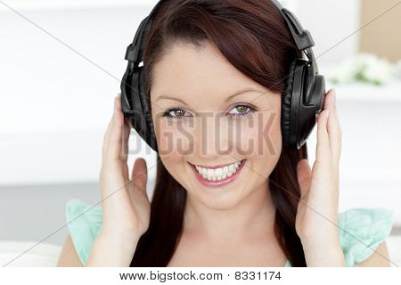 Happy Young Woman Listen To Music Looking At The Camera
