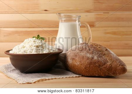 Cottage cheese in clay bowl with jug of milk and loaf of bread on wooden planks background