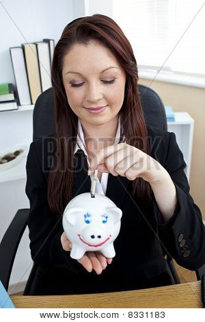 Positive Businesswoman Putting Money Into A Piggy bank