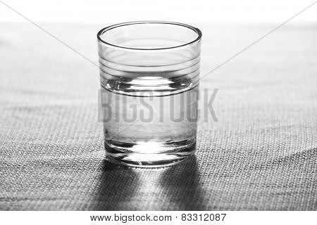 Glass of clean mineral water on burlap cloth background