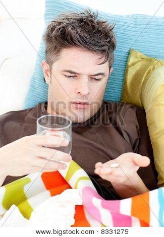 Sick Caucasian Man Taking Pills With Water