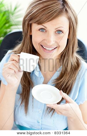 Portrait Of A Delighted Businesswoman Holding A Cup Smiling At The Camera
