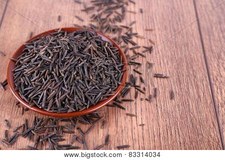 Black rice on plate on wooden background