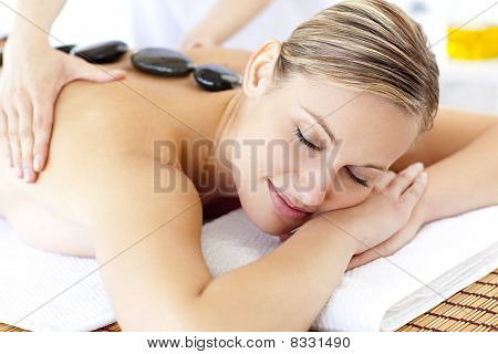 Bright Young Woman Enjoying A Back Massage With Hot Stone