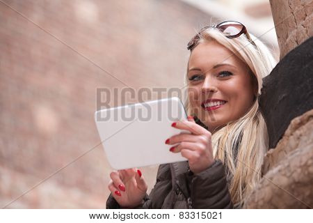 Blonde Smiling Girl Using A Tablet Outdoors