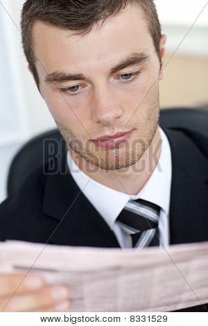 Portrait Of A Serious Businessman Reading The Newspaper