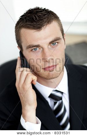 Assertive Young Businessman Talking On Phone Looking At The Camera