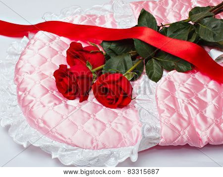 Red Roses And Scarlet Ribbon On Pink Satin.