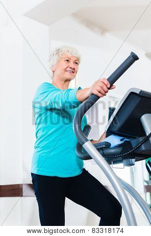 Senior woman on elliptical trainer exercising in gym