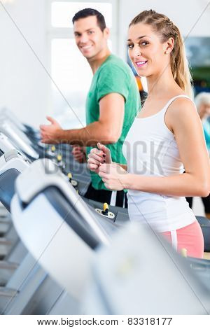 Couple on treadmill in fitness gym running for sport