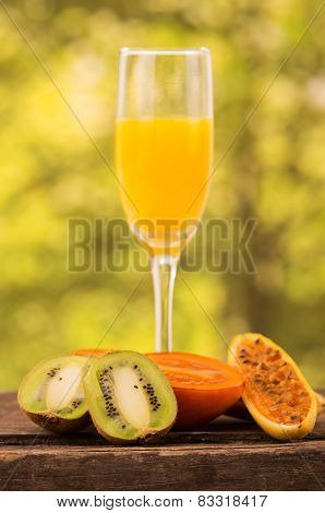 glass of juice with  kiwi, tree tomato and banana passionfruit slices on a wooden table