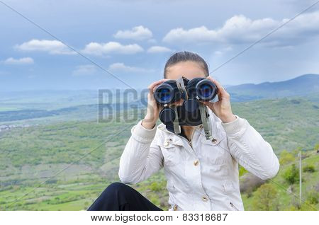 Little girl with binoculars exploring the mountain range