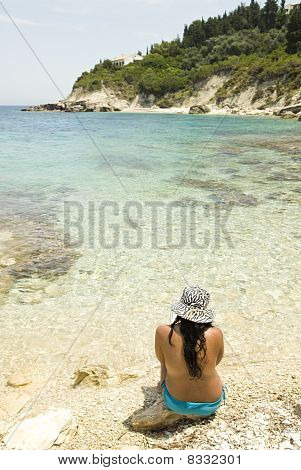 Asian woman sitting on a rocky beach