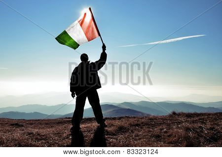 Winner waving Italian flag on the top of a mountain