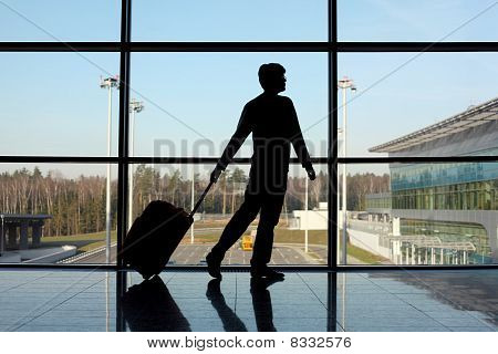 Silhouette Of Man With Luggage Walking Right Near Window In Airport