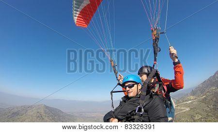 Tourist paragliding with a pilot guiding