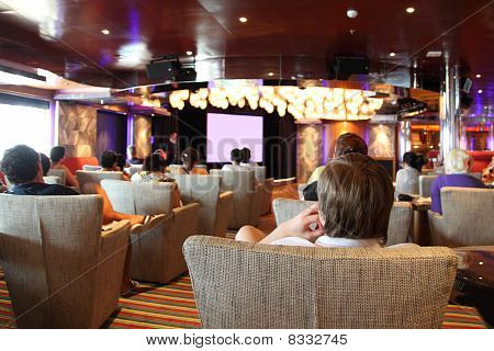 Group Of People At Cruise Liner Cinema Looking At Screen View From Back, Guide Telling About Cruise