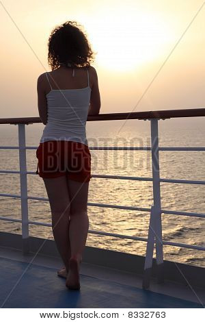 Girl Standing At Ship Deck And Looking Into The Distance View Fr