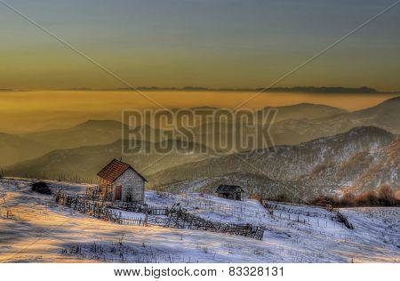 Fog over mountain range at sunset