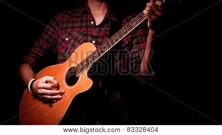 Long hair guy playing guitar acoustic