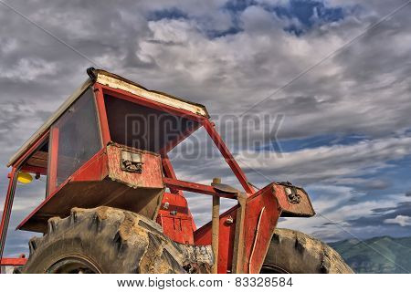 Old tractor against white clouds