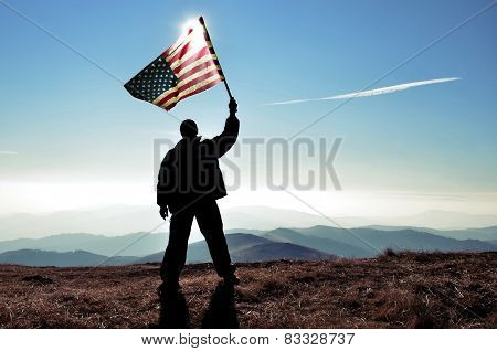 Man holding USA flag on top of a mountain