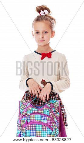 very serious little schoolgirl with satchel in hand.