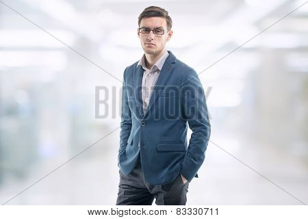 Young handsome guy wearing glasses in the office and standing alone with his hands pockets