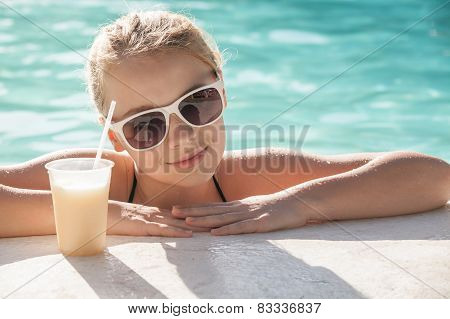 Little Blond Girl With Glass Of Cocktail In The Swimming Pool